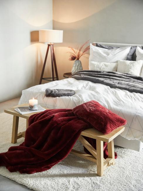 Sypialnia z łóżkiem z białą pościelą oraz szarym kocem i drewnianą ławką oraz lampą w rogu