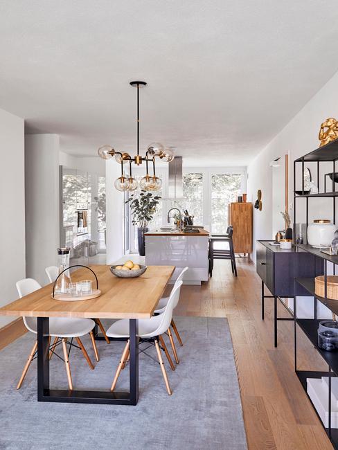 Jadalnia w stylu skandynawskim z drewnianym stołem, białymi krzesłąmi oraz metalową półką