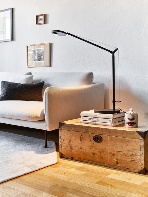 Zbliżenie na szarą sofę z czarną poduszka, jasnym dywanem oraz drewnianą szafką