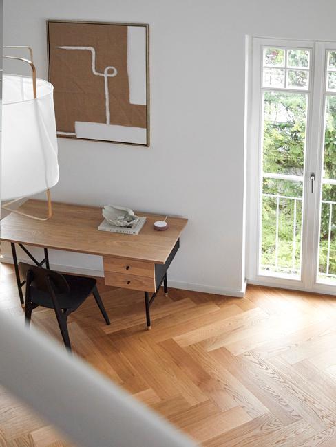 Kącik do pracy z drewnianym biukiem oraz czarnym krzesłem