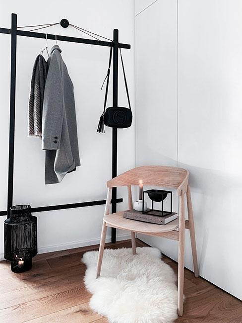 Minimalistyczny przedpokój z drewnianym krzesłem w stylu skandynawskim, czarnym wieszakiem stojącym na ubrania i futranym dywanikiem