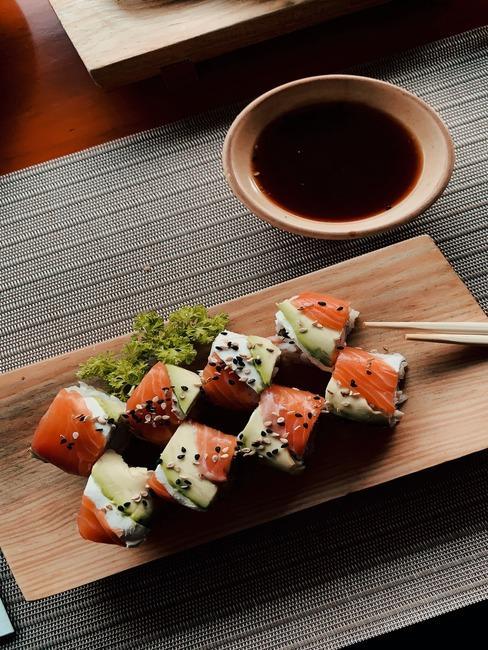 Drewniana deska z maki sushi z ogórkiem i wędzonym łososiem obok miseczki z sosem sojowym