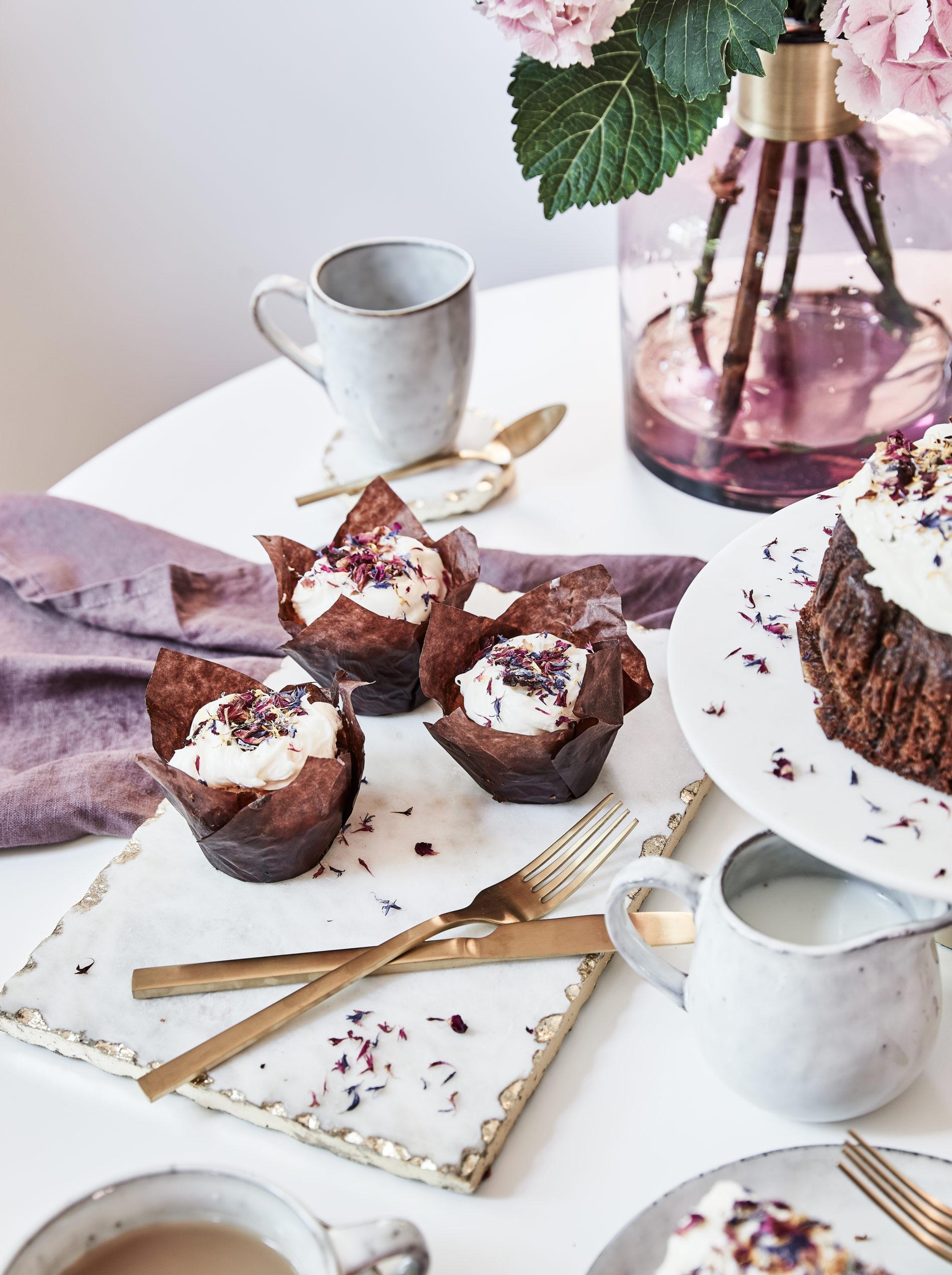 Trzy czekoladowe babeczki na stole obok białej patery z ciastem czekoladowym