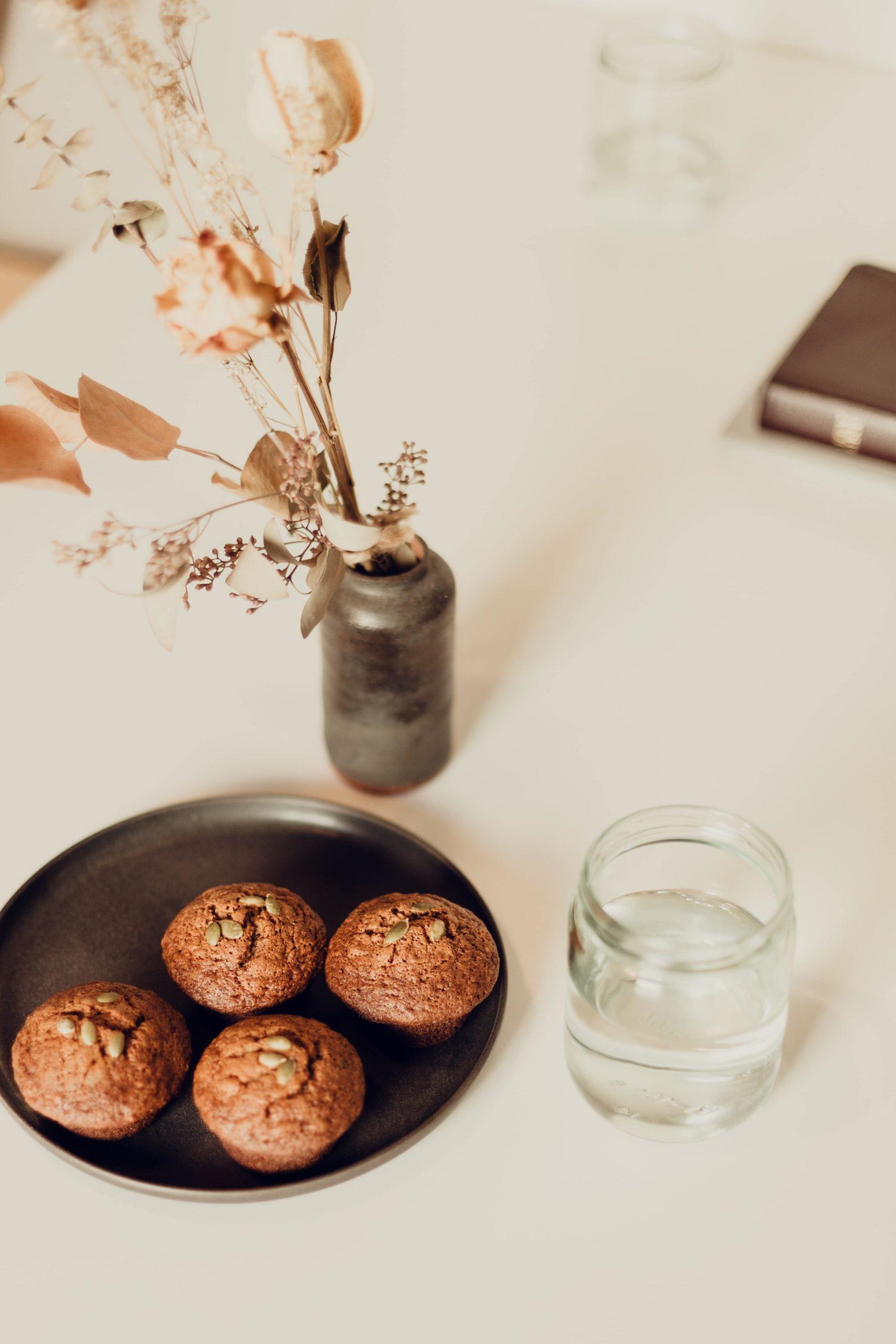Owsiane babeczki na czarnym talerzu obok szklanki oraz wazonu z suszoną kompozycją