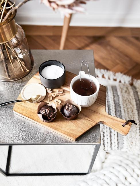 Drewniana deska do krojenia z babeczkami obok białego kubka oraz cukierniczki na stoliczku kawowym
