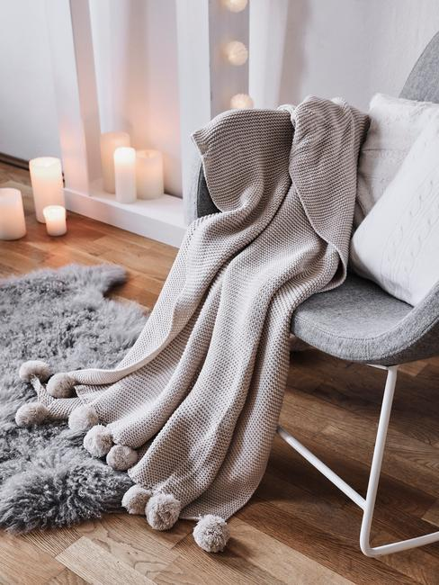 Zbliżenie na szary fotel z kocem i białą poduszką w kąciku z szarym dywanem z owczej skóry oraz świecami