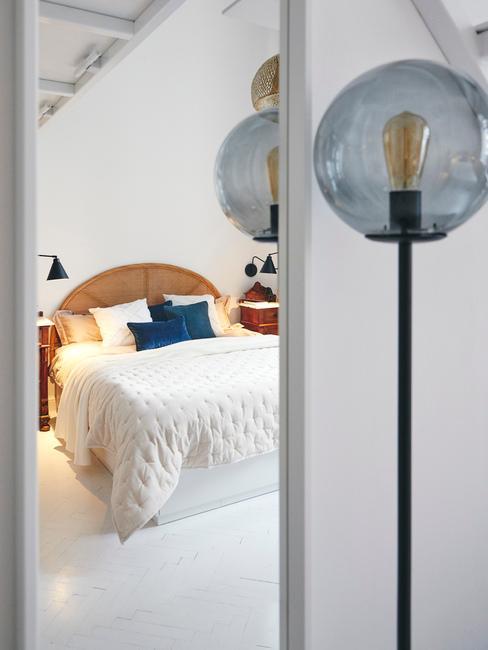 Zbliżenie na lampę i białą sypialnię z łóżkiem o drewnianym zagłówku, niebieską poduszką