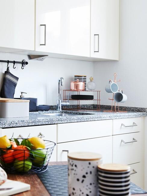 Kuchnia w bloku w stylu skandynawskim z białymi szafkami granitowym blatem, relingiem oraz drewnianym stołem