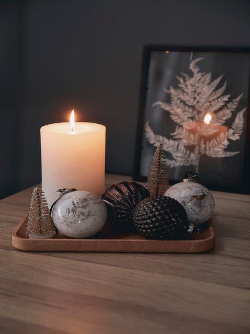 Świąteczna taca dekoracyjna z bombkami choinkowymi, świeczką oraz małymi choinkami na komodzie