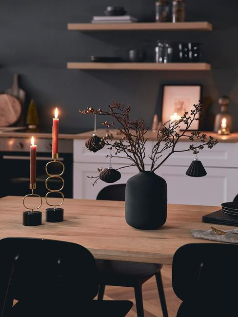 Drewniany stół z wazonem z udekorowami bombkami gałązkami oraz dwoma świecami w kuchni