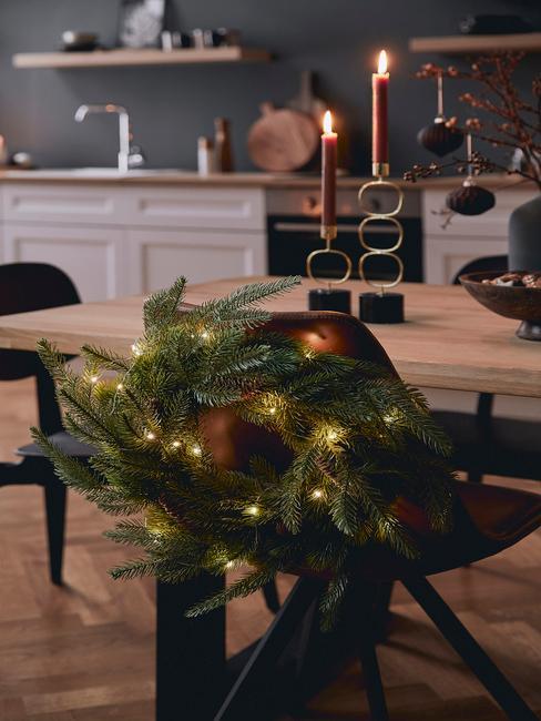 Zbliżenie na wieniec świąteczny doczepiony do tapicerowanego krzesła w jadalni