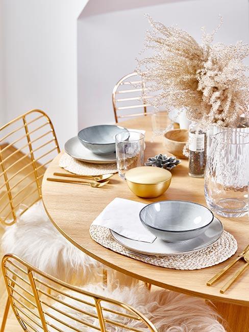Okrągły stół do jadalni z jasnego drewna zastawiony szaroniebieską zastawą z kamionki z trawą pampasową w wazonie i złotymi sztućcami