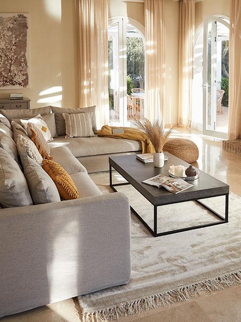 Jasny duży salon pełen słońca z szarą sofą i żółtymi poduszkami