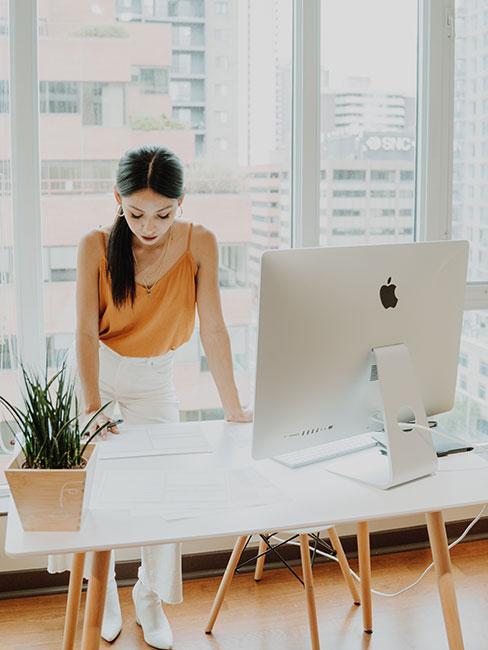 Kobieta w jasnym biurze nachylająca się nad biurkiem
