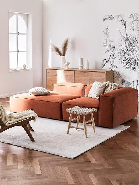 Salon w stylu boho z sofą modułową w kolrze terakoty i tapetą w szare kwiaty