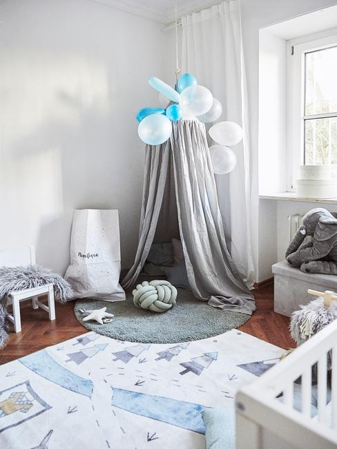 Kącik do zabawy w pokoju dziecięcym z szarym namiotem, balonikami, poduszka supłem oraz okrągłym dywanem