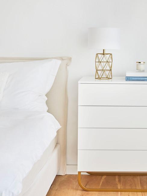 Zbliżenie na białą komodę ze złota lampką obok książek w białej sypialni