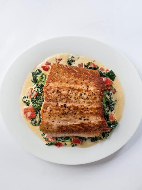Biały talerz z pieczonym łososiem w sosie ze szpinaku