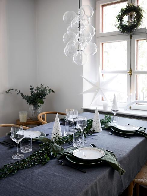 Stół świąteczny szarym obrusem, świerkową girlandą, świeczkami w kształce choinki oraz białymi talerzami