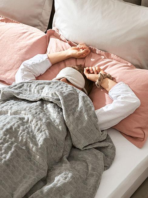 Kobieta śpiąca za maską na oczach pod kołdrą terapeutyczną