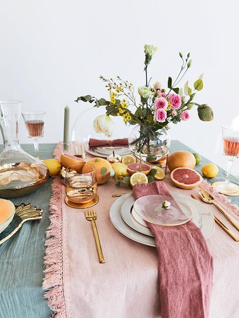 stół zastawiony pastelowa zastawą i tekstyliami z pomarańczami i kolorowymi kwiatami w wazonie