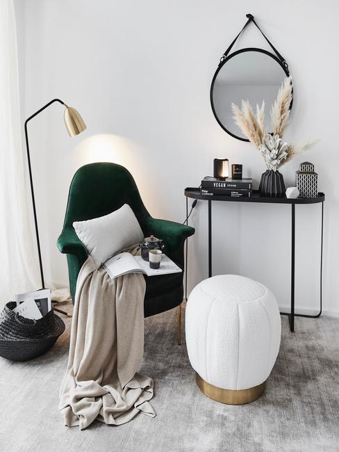 Zbliżenie na kącik ze szmaragdowym krzesłem, kocem, złotą lampą, czarną konsolą i lustrem
