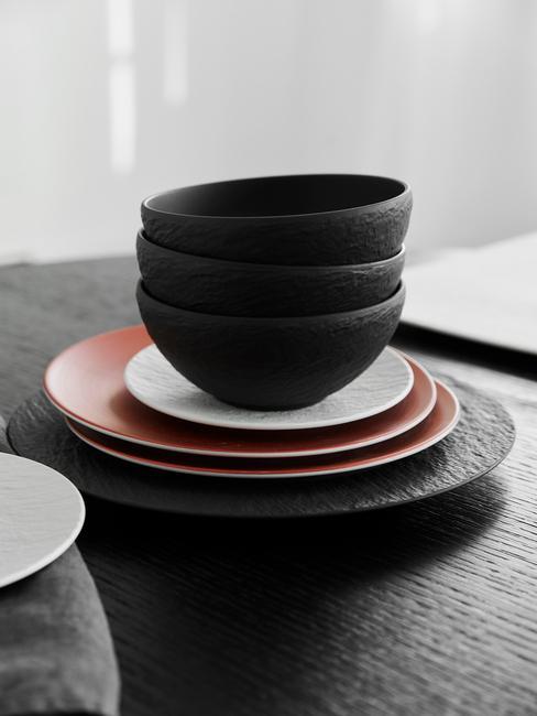 Zestaw czarnej, czerwonej i białej ceramik na czarnym blacie