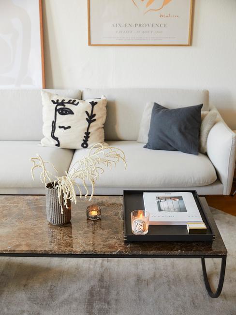 Zbliżenie na beżową sofę z poduszkami oraz czarny stolik kawowy z dywanem