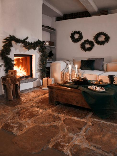 Wnętrze salonu w stylu wiejskim, z betonową podłogą, białą sofą z poduszkami, drewnianym stolikiem z dekoracjami i kominkiem
