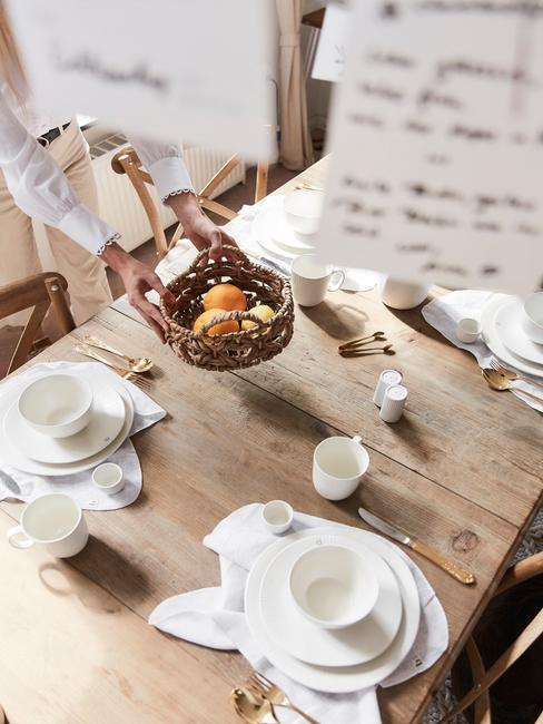 Drewniany stół z białym zestawem talerzy, plecionym koszykiem