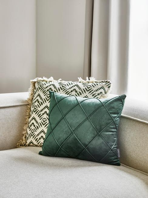 Zbliżenie na beżową sofę z dwoma poduszkami w przygaszonych kolorach