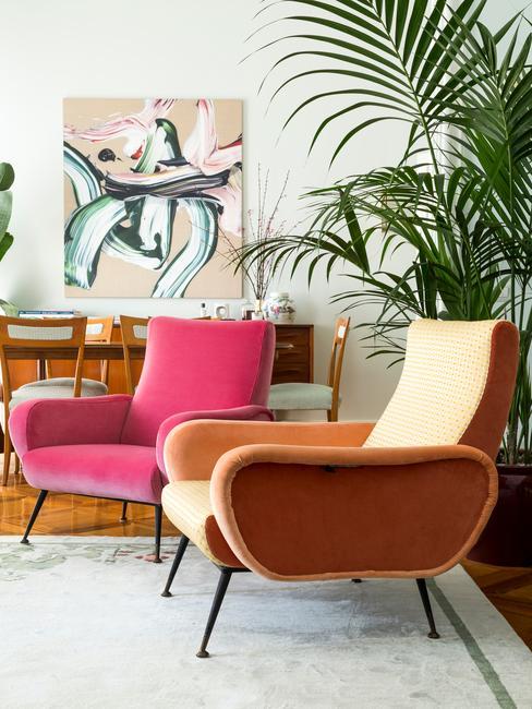 Zbliżenie na dwa krzesła w mocnych barwach różu i pomarańczy w salonie z dużą rośliną w doniczce