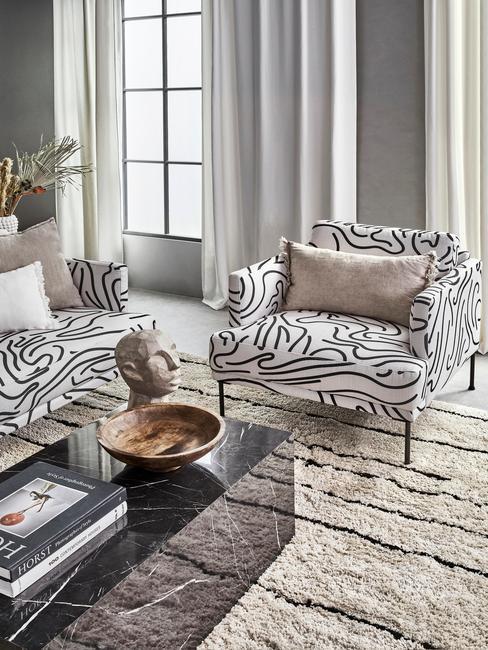 Salon z meblami wypoczynkowymi w geometryczne wzory, stolik z czarnego marmuru z dekoracjami oraz biało - czarnym dywanem