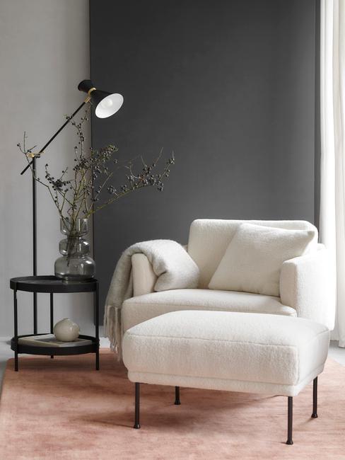 Zbliżenie na kącik do czytania z białym fotele z boucle, czarnym stoliczkiem z waoznem z suszoną kompozycją oraz lampą