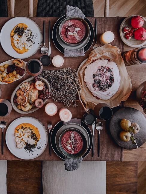 Drewniany stół z białą zastawą oraz kolacją dla przyjaciół