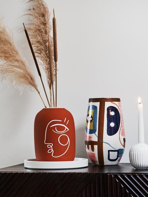Zbliżenie na dwa kolorowe wazony na białej tacy dekoracyjnej oraz świecznik z świeczką