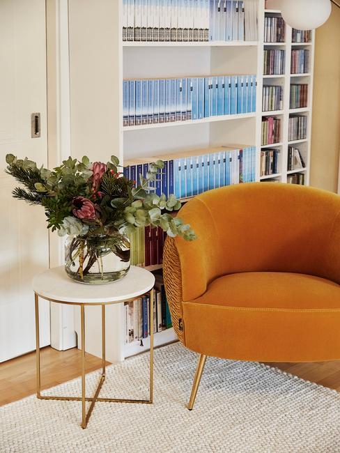 Kącik z pomarańczowym fotelem, biało - złotym stoliczkiem pomocnicznym oraz białym regałam z książkami