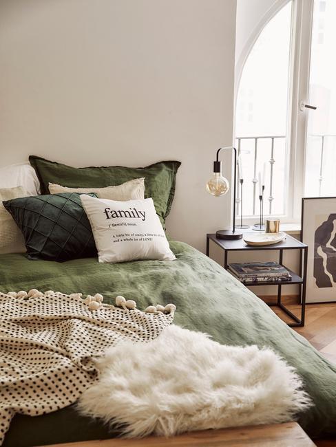 Zbliżenie na łóżko w białej sypialni z zieloną pościlą, białymi poduszkami, beżowym pledem oraz czarnym stoliczkiem nocnym