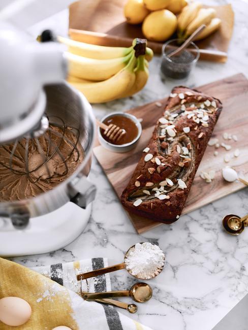 Chlebek bananowy na drewnianej desce do krojenia obok białego robota kuchennego na marmurowym blacie