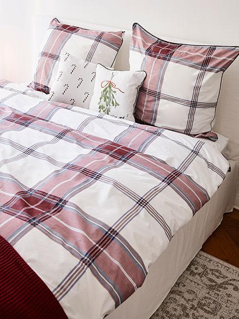 pościel w kratę na łożku oraz poduszki dekoracyjne w świąteczne wzory