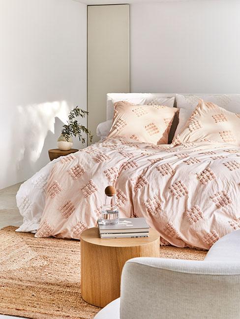 Jasna sypialnia z jasnoróżową pościelą z tuftowaną dekoracją