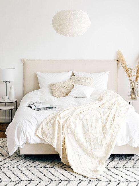 Naturalna sypialnia z kremową pościelą i wiszącą lampą z piór