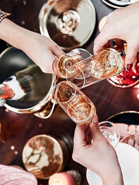 Zbliżenie na trzy ręce wznoszące toast kieliszkami z szampanem na tle udekorowanego stołu
