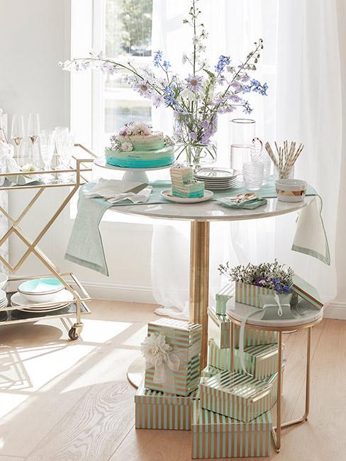 Prezenty opakowane w turkusowo złoty paier pod stolikiem pomocniczym ze złota, na którym stoją kwiaty w wazonie i turkusowy tort
