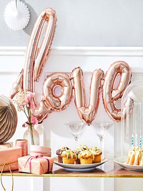różowy balon w kształcie napisu love na białoszarej ścianie przy stoliku z ciastkami i dekoracjami