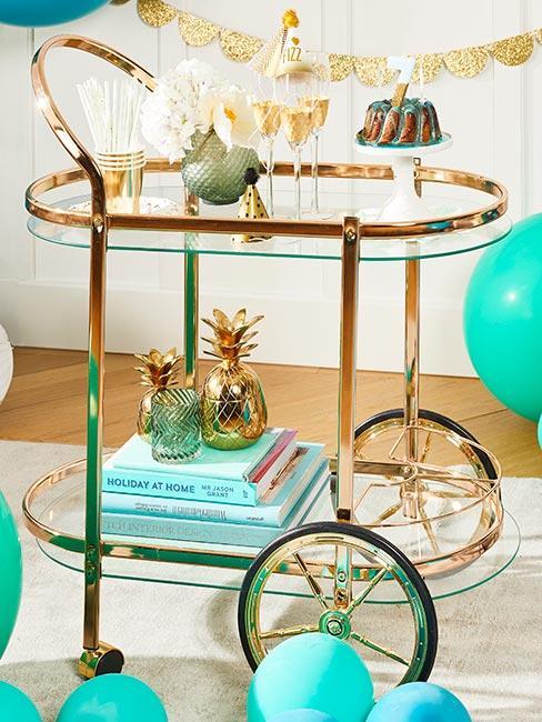złoty wózek barowy na kołach udekorowany złotymi ananasami, kileiszkami do szampana i ciastem