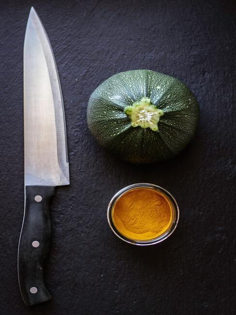 Czarna deska z nożem do krojenia, dynią oraz słoiczkiem kurkumy