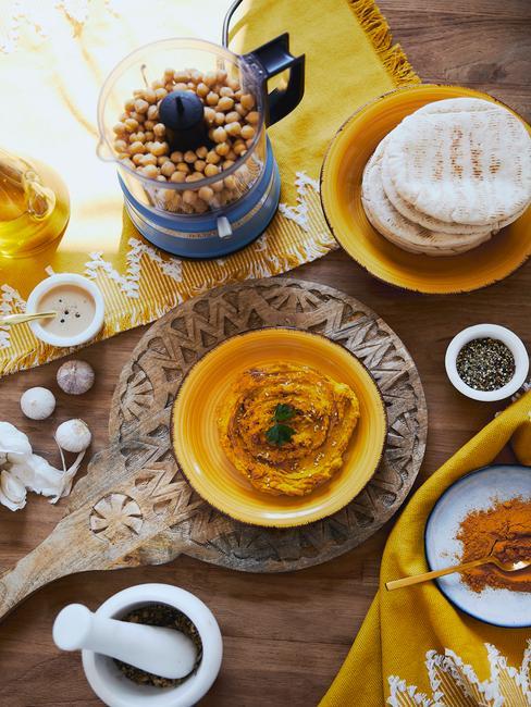 Hummus z kurkumą na żółtej miseczce obok talerzyka z chlebkiem pita, niebieskim mikserem oraz talerzykiem z kurkumą