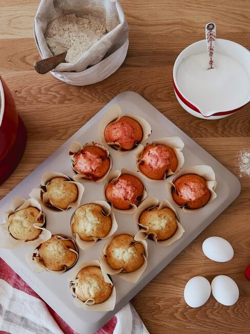 Metalowa blaszka babeczek obok jajek i miską z masą na babeczki