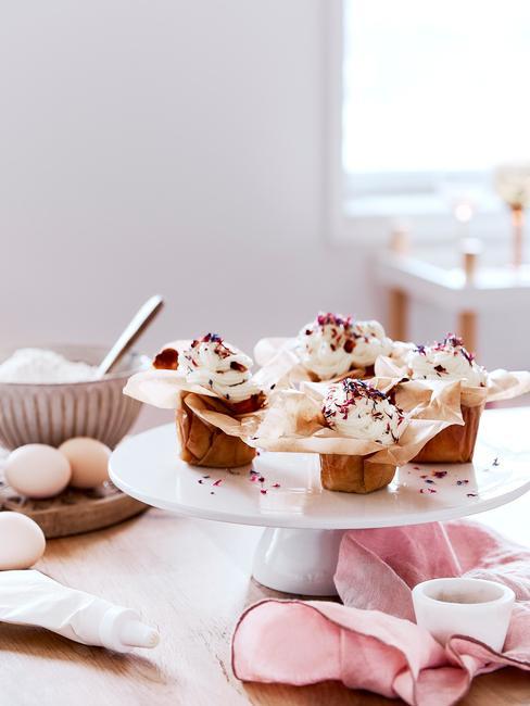 Biała patera na blacie kuchennym z babeczkami obok miseczki z mąką